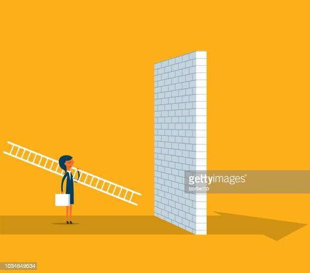 Businesswoman standing in front of a large brick wall