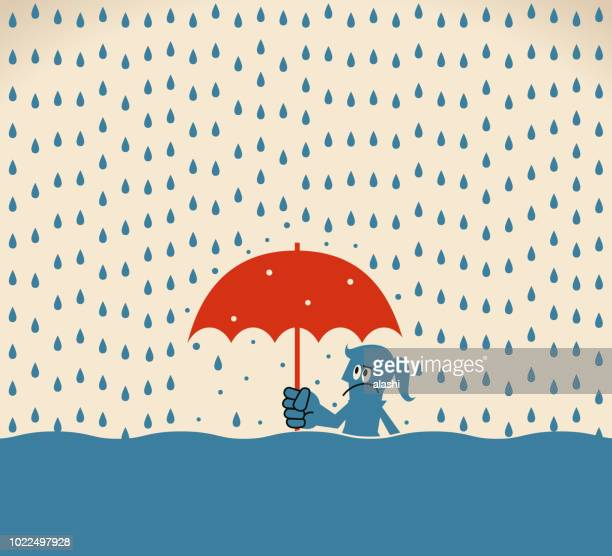 Businesswoman with umbrella standing in a flood of rain