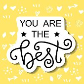 calligraphy lettering of You are the best in black with white outline on yellow background with hearts