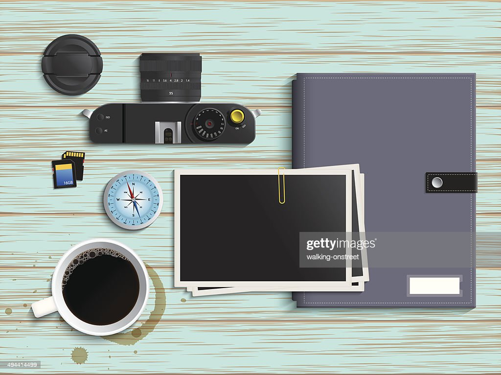 Camera, coffee, compass and colorful diary on Vintage table
