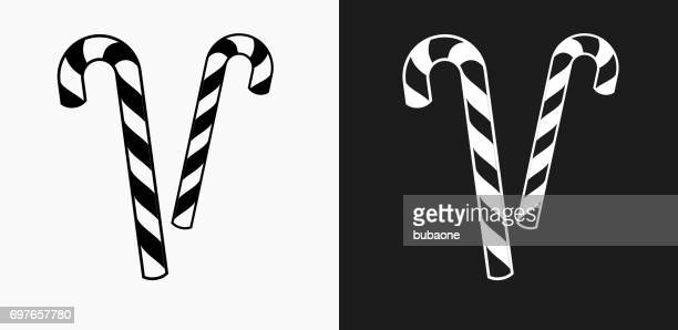 candy canes icon on black and white vector backgrounds - candy cane stock illustrations