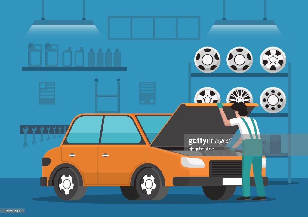 Car mechanic fixing car in auto repair garage.