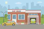 Car wash station and two cars on city background.