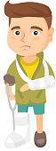 Caucasian sad injured boy with broken arm and leg