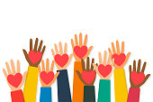 Charity, volunteering and donating concept. Raised up human hands with red hearts. Children's hands are holding heart symbols