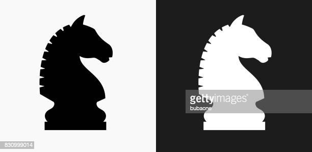 chess knight icon on black and white vector backgrounds - chess stock illustrations