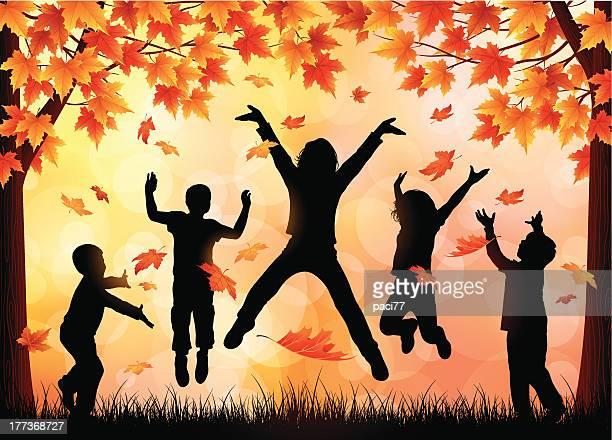 Crianças brincando em folhas