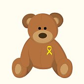 children's toy with a yellow ribbon as a symbol of childhood cancer