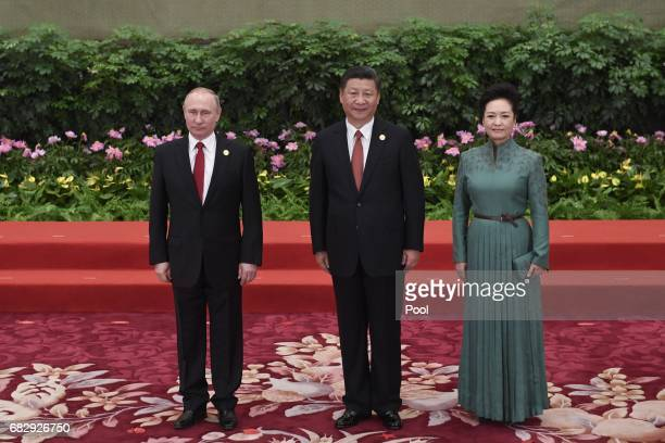 Chinese President Xi Jinping and his wife Peng Liyuan poses with Russian President Vladimir Putin for a photo at the Great Hall of the People in...
