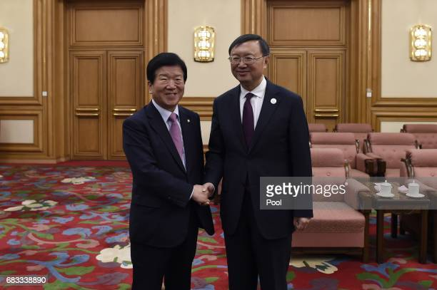 Chinese State Councillor Yang Jiechi shakes hands with South Koreas special representative for the Belt and Road Forum Park Byeong Seug of the ruling...