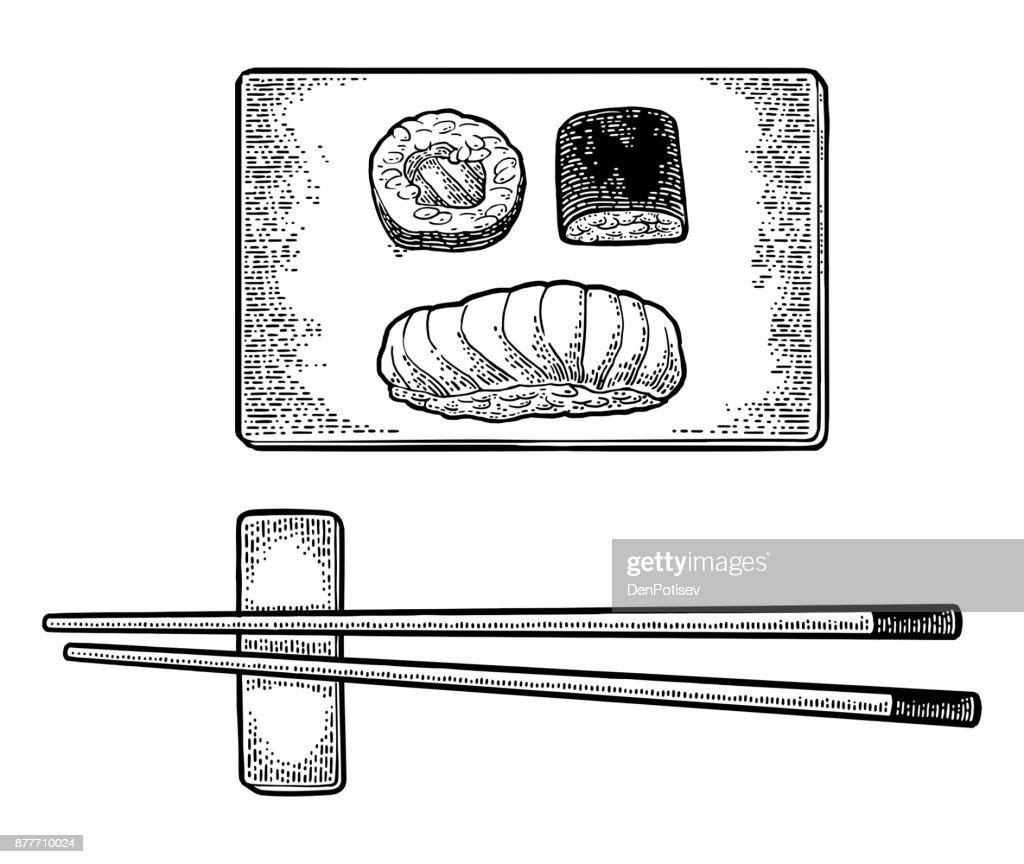 Chopsticks Nigiri Sushi with fish, rolls on wood board.