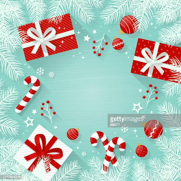 christmas background with decorations and gift boxes, white fir tree branches on wooden table - candy cane stock illustrations