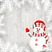Christmas background with white branches and snowman on old white wooden background.