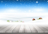 Christmas background with wooden table looking out to snowy landscape