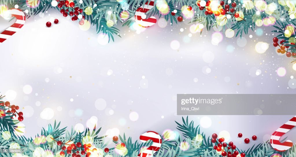 Christmas border or frame with fir branches, berries and candy isolated on snowy background.