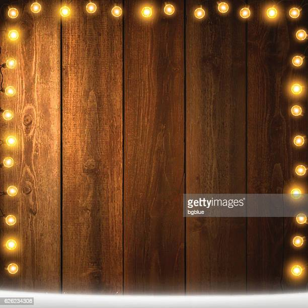 Christmas Lights on lit blank wooden background with snow