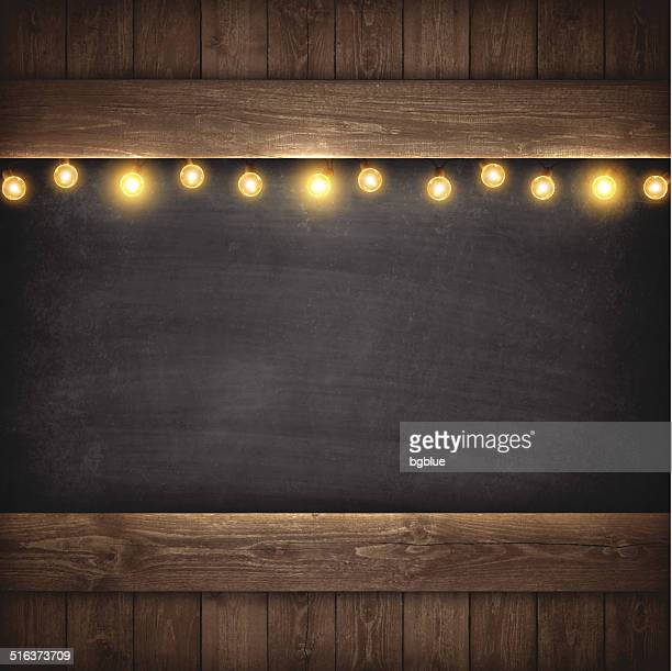 christmas lights on wooden boards and chalkboard - brown stock illustrations