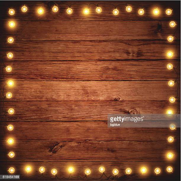 christmas lights on wooden texture - construction frame stock illustrations