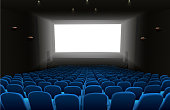 Cinema auditorium with blue seats and white blank screen