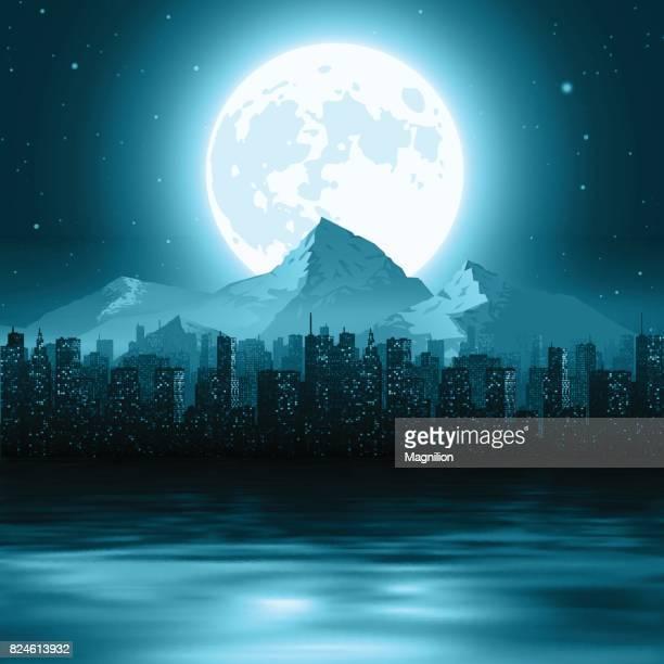 Ein Stadtbild mit Bergen am Horizont durch das Wasser in der Nacht