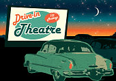 Classic Drive-In Theatre with cars and  sign at dusk