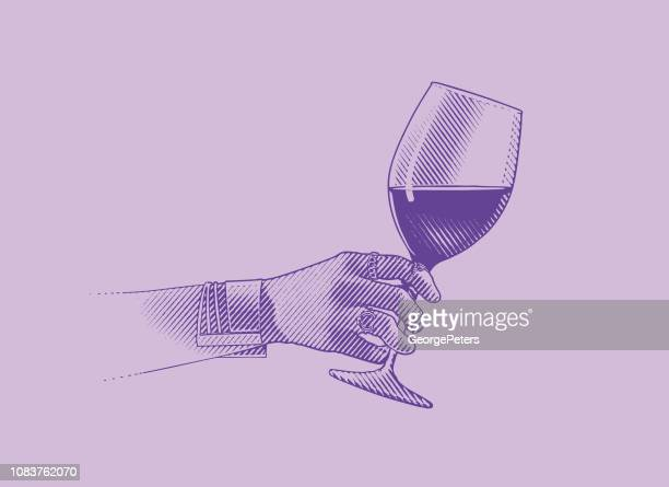 Close up of glass of wine and woman's hand