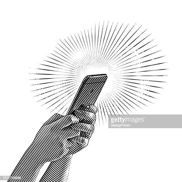 close up of hands holding smart phone - engraving stock illustrations