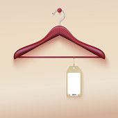Clothes hanger with tag isolated on cream background