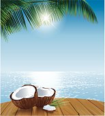 Coconuts on Table Ocean and Palmleaves