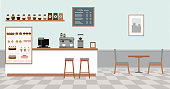 Coffee shop with white bar counter, table and chairs.