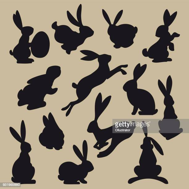 collection of black easter rabbit silhouettes - easter bunny stock illustrations