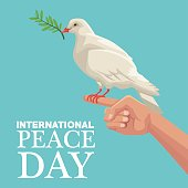 color poster hand holding in finger a pigeon with olive branch in peak international peace day text