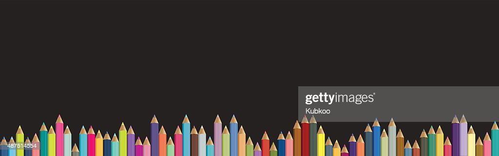 Colored pencils background. Black board with isolated crayons.