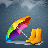 Colorful open umbrella and long boots under heavy rain.