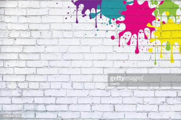 bunte farbe splash splatter grunge weiß ziegel wand hintergrund - streetart stock-grafiken, -clipart, -cartoons und -symbole