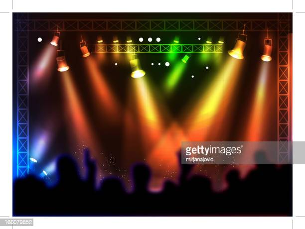 Colorful spotlights over a silhouette crowd at a concert