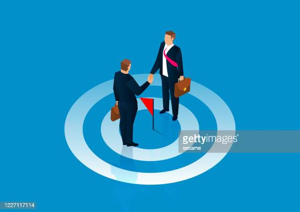 common goal, reach agreement, two businessmen stand on the bullseye and shake hands - new hire stock illustrations
