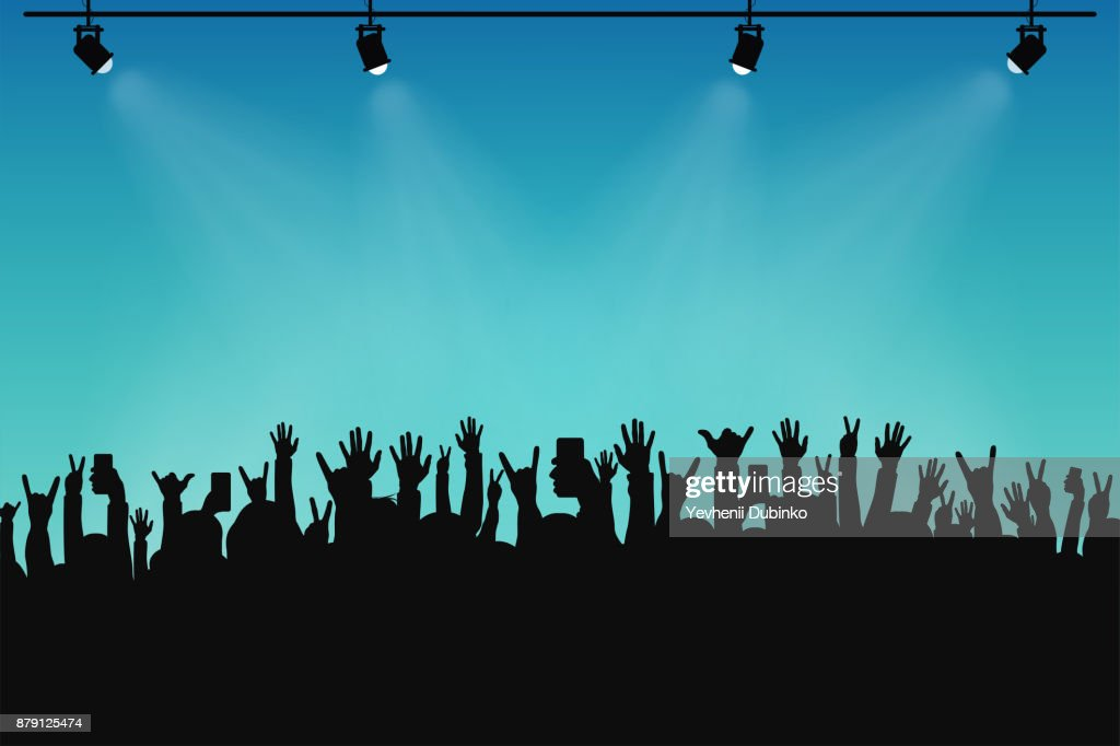 Concert crowd, people silhouettes. Hands with different gestures and smartphones in raised hands. Spotlights on stage