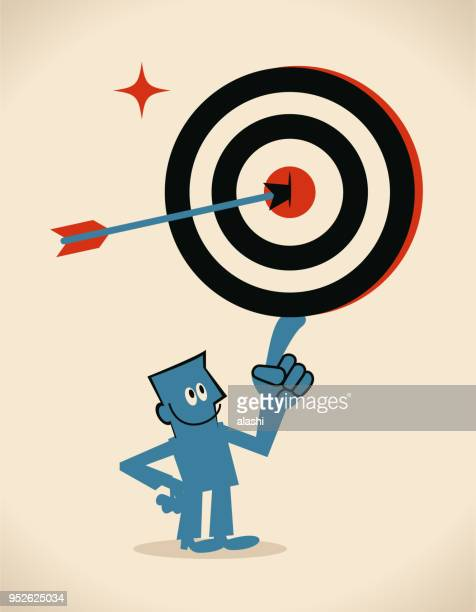 Confident businessman showing a goal target (dartboard) with an arrow on Bull's-Eye