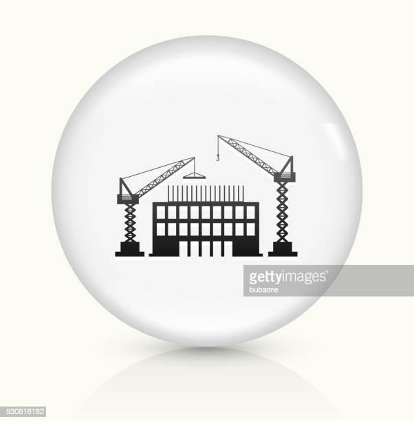 construction building icon on white round vector button - crane construction machinery stock illustrations