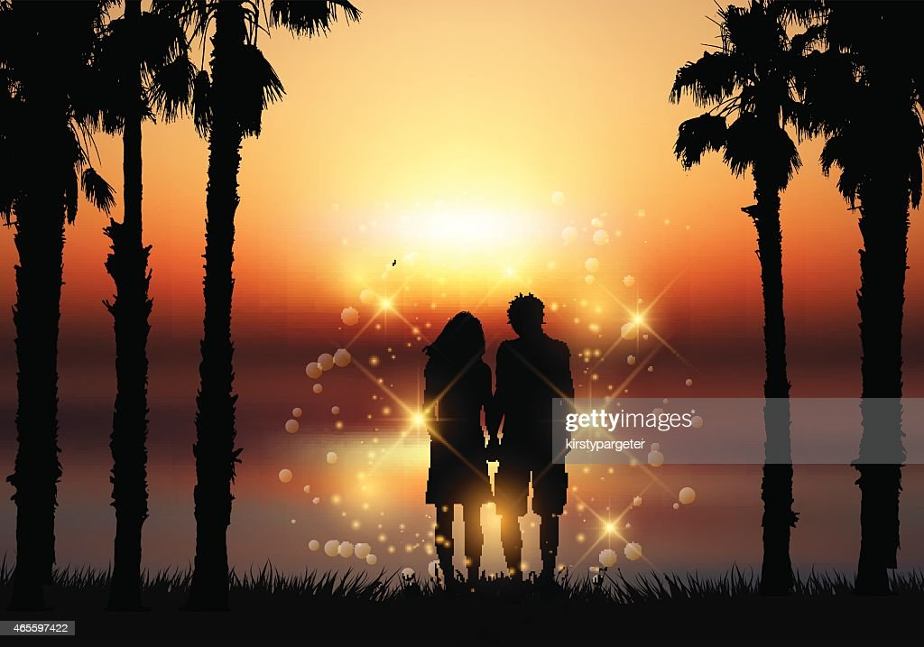 Couple holding hands against a sunset background