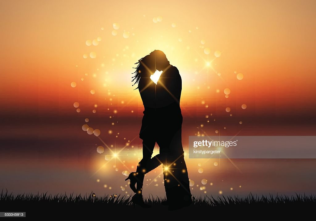 Couple kissing against a sunset background
