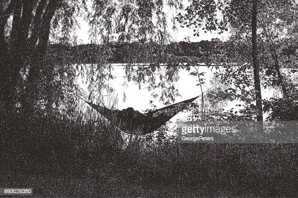 Couple relaxing in hammock on a lake