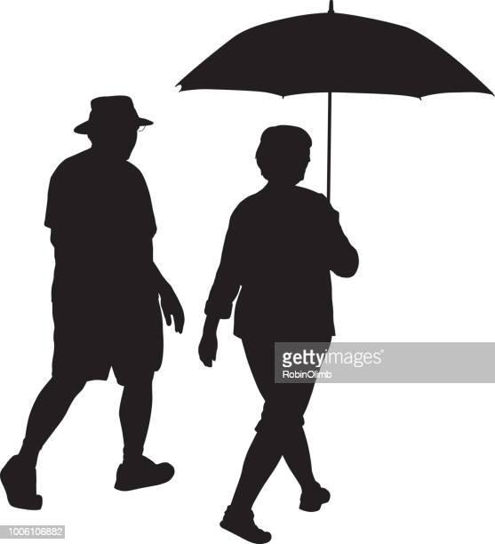 stockillustraties, clipart, cartoons en iconen met paar wandelen met grote paraplu silhouet - oudere mannen