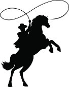 Cowboy silhouette with lasso on horse