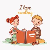 Cute boy and girl reading book