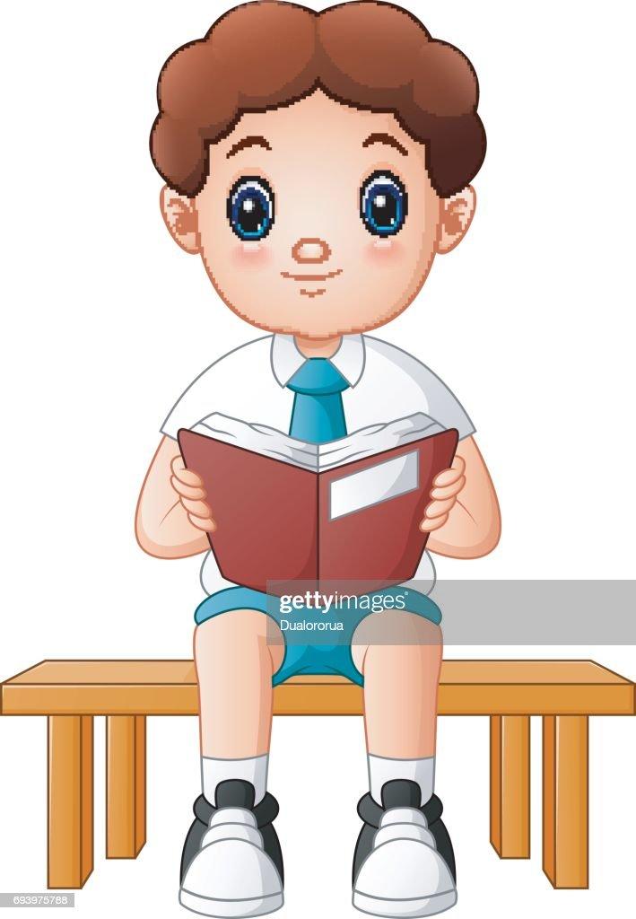 Cute boy in a school uniform reading a book