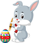 Cute Easter Bunny painting an egg