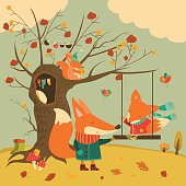Cute foxes ride on a swing in the autumn forest