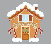 Cute Gingerbread House Covered in Snow and Decorated with Candy